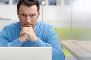 Casual, determined-looking businessman with laptop